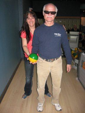Monsieur Antonin Plante se prépare à lancer une boule de quille avec l'aide de madame Isabelle Mathieu.