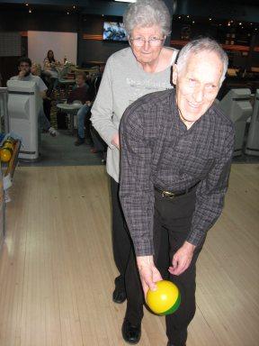 Monsieur Pierre Bissonnette se prépare à lancer une boule de quille avec l'aide de madame Solange Bissonnette.